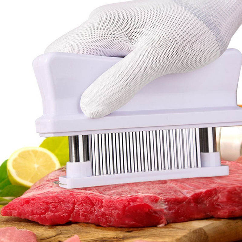 stainless steel blade meat tenderizer piercing through a cut of steak on a cutting board